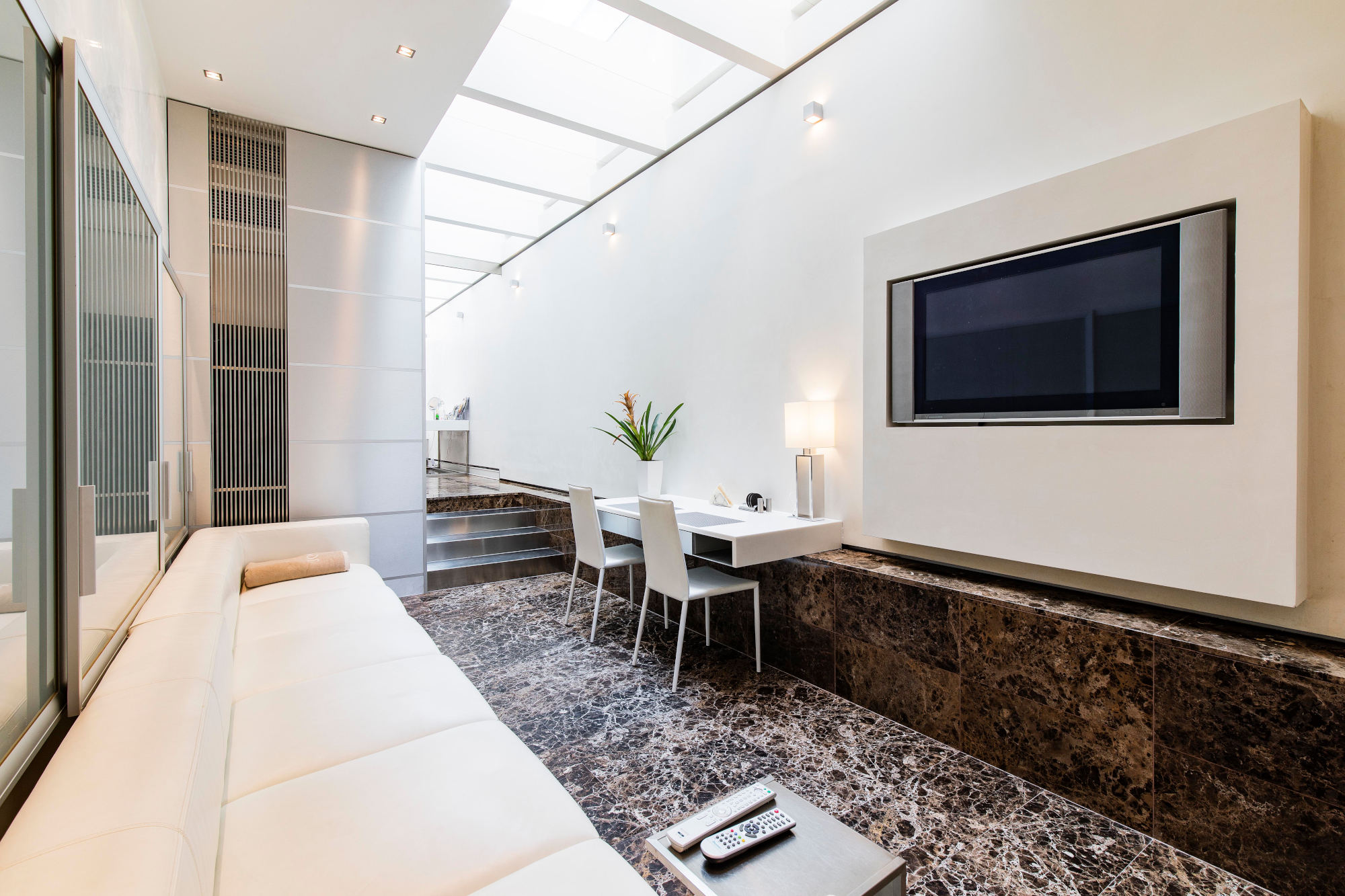 Widescreen TV in front of large white sofa in the living area - couples apartment prague